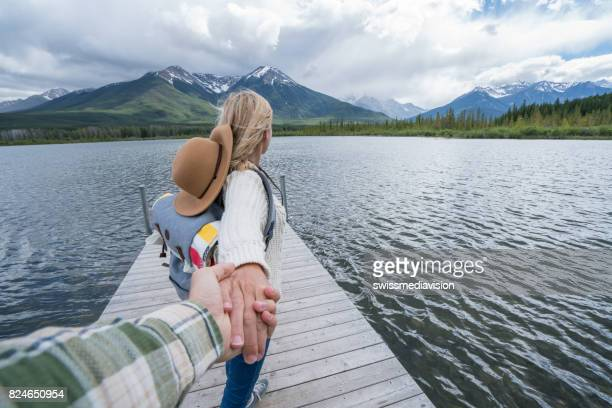 follow me to- young woman leading man on pier above lake - following stock pictures, royalty-free photos & images