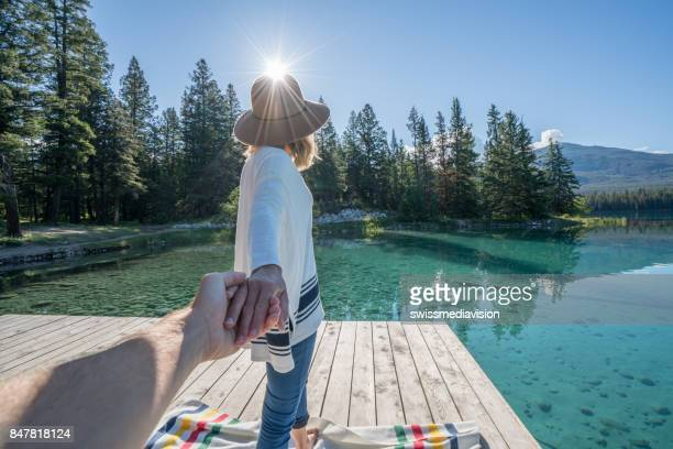 Follow me to- young woman leading man to lake