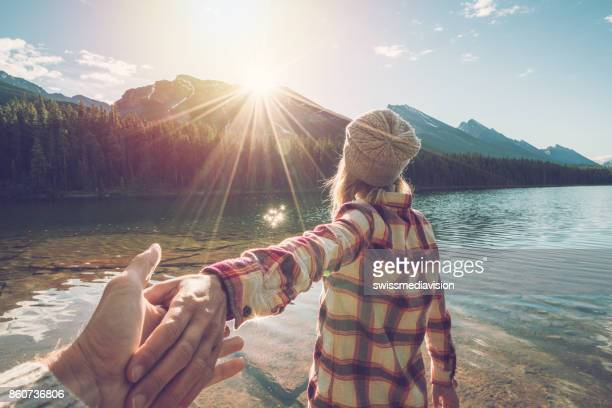 follow me to- young woman leading man to mountain lake at sunrise - following stock pictures, royalty-free photos & images