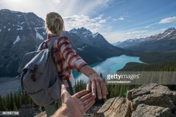 follow me to, young woman leading man to mountain top - following stock pictures, royalty-free photos & images