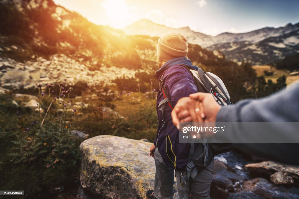 Follow me. Young woman showing the way during hiking activities : Stock Photo