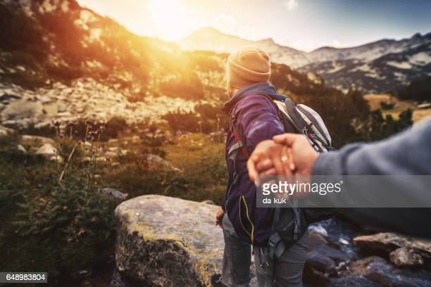follow me. young woman showing the way during hiking activities - following stock pictures, royalty-free photos & images