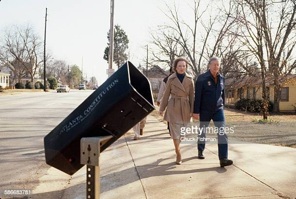 Followed by Secret Service agents American politician and former US President Jimmy Carter and his wife Rosalynn along a sidewalk upon the couple's...