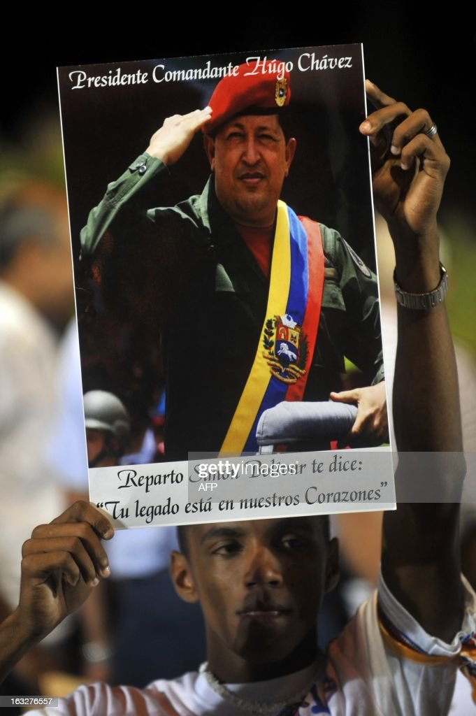 A follower holds a picture of late Venezuelan President Hugo Chavez during an ecumenical service held for him in Managua, on March 6, 2013. The flag-draped coffin of Venezuelan leader Hugo Chavez was borne through throngs of weeping supporters on Wednesday as a nation bade farewell to the firebrand leftist who led them for 14 years. AFP PHOTO/Hector RETAMAL