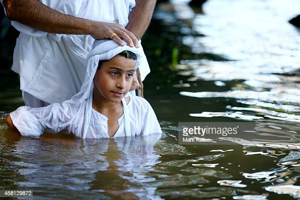 A follower is baptised during a Mandaean baptism ceremony in the Nepean river at Emu Plains on October 26 2014 in Sydney Australia The small western...
