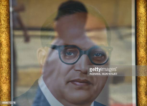 A follower is reflected on a framed photograph of Bhimrao Ambedkar for sale on Ambedkar's 124th birth anniversary near the historic Chaitya Bhoomi...