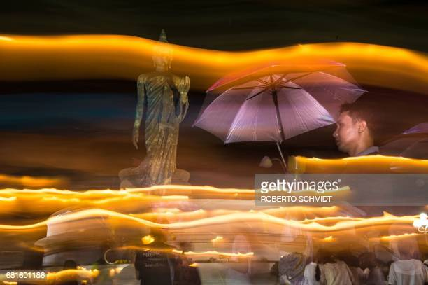 A follower of Bhuddism uses an umbrella during light rain as he and others walk around the giant statue of Lord Bhudda at the Phutthamonthon in...