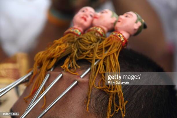 A follower of the Chinese Bang Neow Shrine pierces his forehead with skewers before a procession during the Phuket Vegetarian Festival The Phuket...