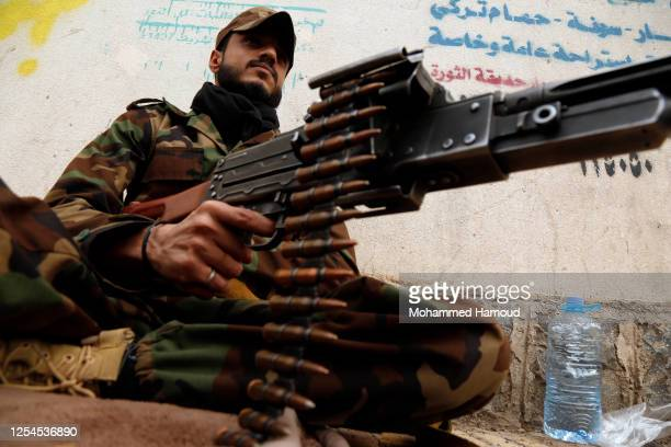 Follower of the Houthis group holds a machine gun as he keeps watch during a tribal gathering against the Saudi-led coalition war on Yemen on July...