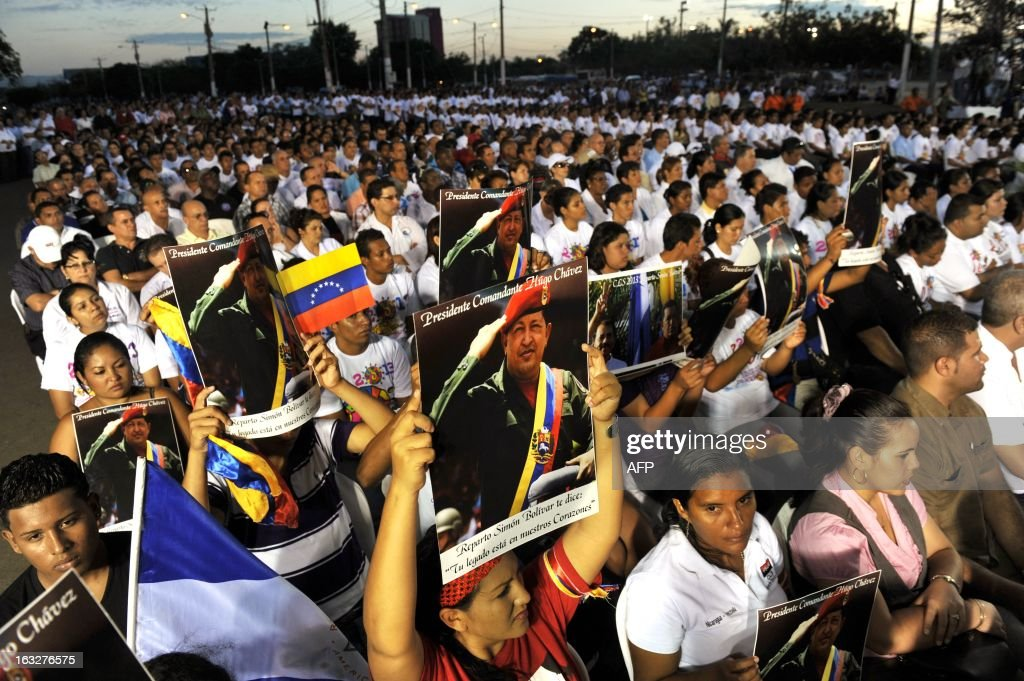Followers hold pictures of late Venezuelan President Hugo Chavez during an ecumenical service held for him in Managua, on March 6, 2013. The flag-draped coffin of Venezuelan leader Hugo Chavez was borne through throngs of weeping supporters on Wednesday as a nation bade farewell to the firebrand leftist who led them for 14 years. AFP PHOTO/Hector RETAMAL