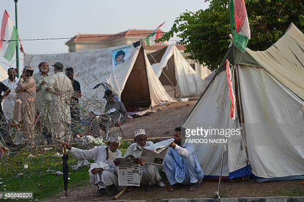 Followers of Canadabased populist cleric TahirulQadri read newspapers during an antigovernment protest in front of the Parliament in Islamabad on...