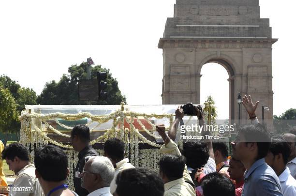 Followers of former Prime Minister Atal Bihari Vajpayee take part in the last rites as his funeral procession passes by ITO crossing on August 17...