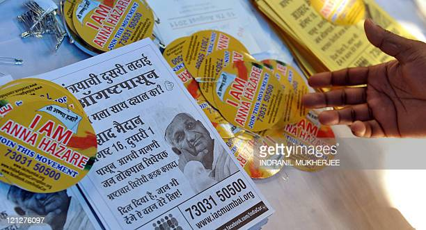 Followers of Indian social activist Anna Hazare collect badges and pamphlets to show their support for Hazare in Mumbai on August 16 2011 Indian...