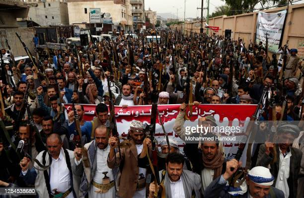 Followers of the Houthis group hold up their guns as they shout slogans during a tribal gathering against the Saudi-led coalition war on Yemen on...