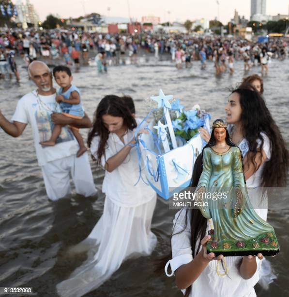 Followers of the Umbanda AfroAmerican take part in a ritual offering tribute to Iemanja the African goddess of the sea in Montevideo on February 2...
