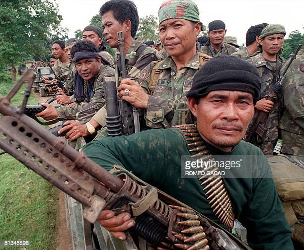 Following a ceasefire agreement, two truckloads of battle-weary army soldiers ride out from the frontline area in Matanog town near the main Moslem...