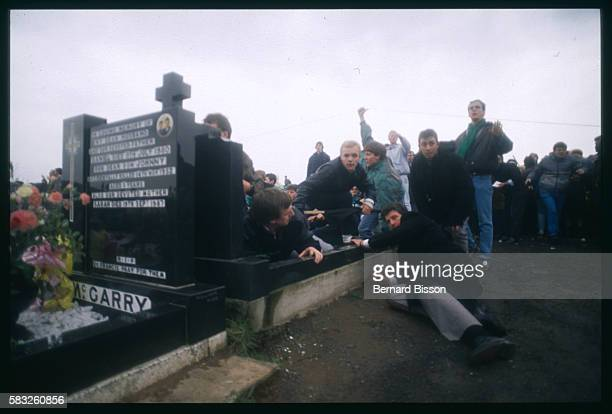 Following a grenade attack people hide behind a tomb in a cemetery during the funeral for three IRA members