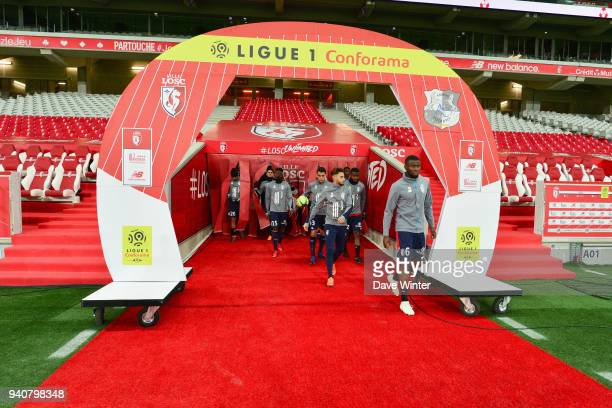 Following a recent pitch invasion no supporters are allowed into the stadium as Ibrahim Amadou of Lille leads his teamout to warm up before the Ligue...