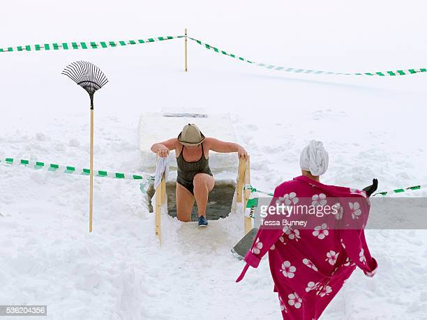 Following a sauna a female ice swimmer waits while another gets out after a brief dip in a hole in the ice Tuomiojarvi Jyvaskyla Central Finland Ice...