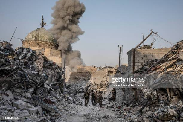 Following an airstrike from coalition forces soldiers with Iraqi special forces walk through a debrisstrewn alley after they regained control over...