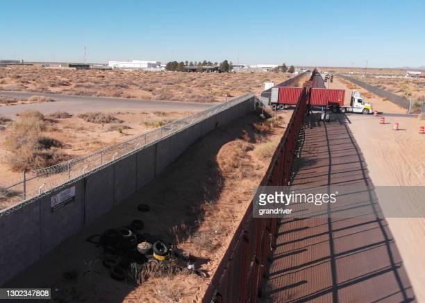 米国メキシコ国境の壁を通過し、商品を輸入するために米国税関に行くコンテナセミトラックのドローンクリップに続いて - 国境 ストックフォトと画像