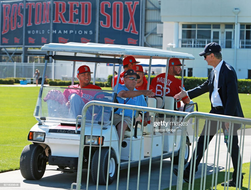 Following his press availability, Boston Red Sox owner John Henry, right, shakes hands with a member of the Jet Blue security staff who was driving a group of pitchers out to the back fields on the day of the first full squad spring training workout at the Player Development Complex at Jet Blue Park in Fort Myers, FL on Feb. 19, 2018.
