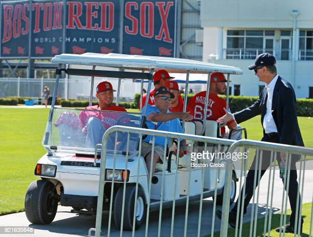 Following his press availability Boston Red Sox owner John Henry right shakes hands with a member of the Jet Blue security staff who was driving a...