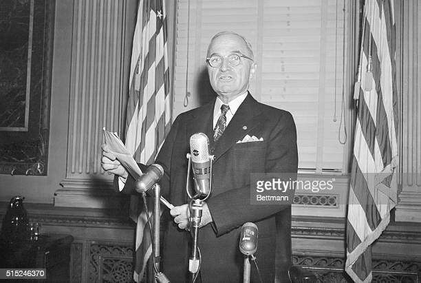 Following his press conference today President Harry S Truman poses for photographers reading the statement in which he grimly warned Communist...