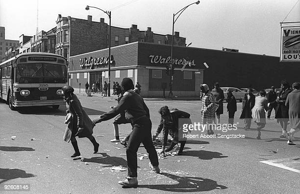 Following looting in the area pedestrians drag debris from the street in front of a city bus at the intersection of West Madison Avenue and Oakley...