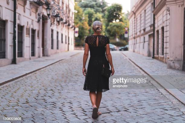 following one woman in black cocktail dress walking alone through empty city steert of old town - cocktail dress stock pictures, royalty-free photos & images
