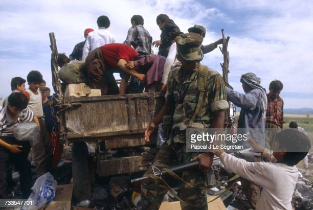 Following Operation Desert Storm, an American soldier stands by as a truckload of Kurdish refugees prepare to leave Iraq for camps in the West Bank....