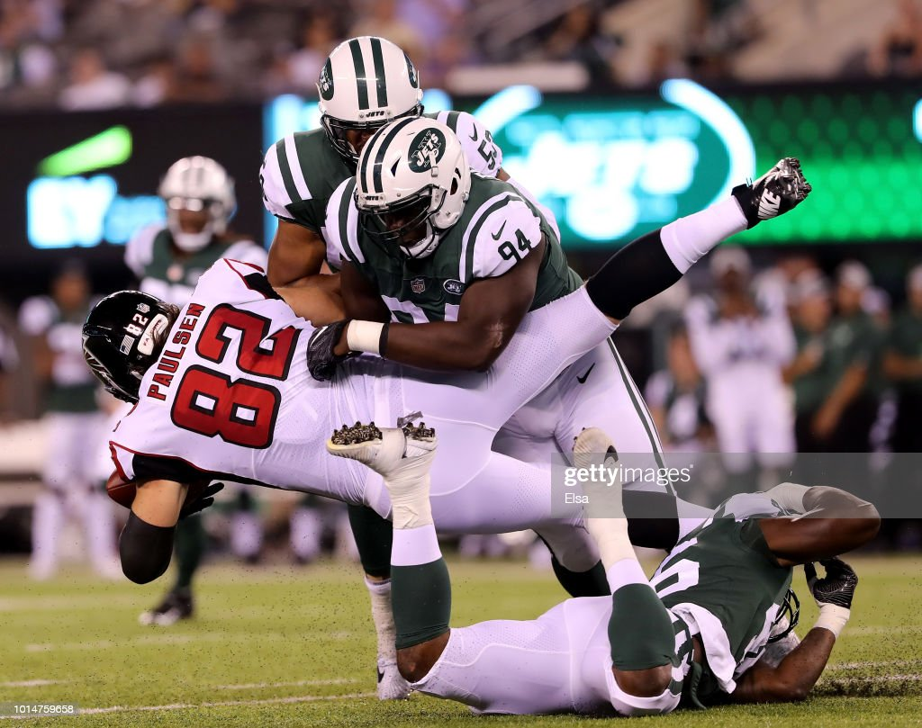 Folorunso Fatukasi #94 of the New York Jets tackles Logan Paulsen #82 of the Atlanta Falcons in the first half during a preseason game at MetLife Stadium on August 10, 2018 in East Rutherford, New Jersey.