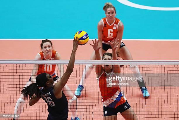 Foluke Akinradewo of United States spikes the ball against Robin de Kruijf Lonneke Sloetjes and Maret BalkesteinGrothues of Netherlands during the...