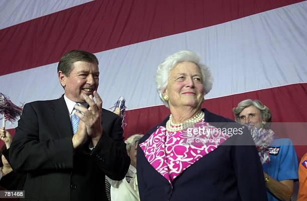 Fomer first lady Barbara Bush receives applause from U.S. Senator John Ashcroft, R-MO, after speaking at a republican rally October 26 , 2000 at...