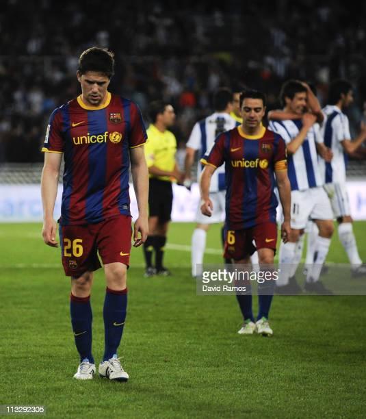 Fontas and Xavi Hernandez of FC Barcelona look down dejected at the end of the La Liga match between Real Sociedad and Barcelona at Estadio Anoeta on...