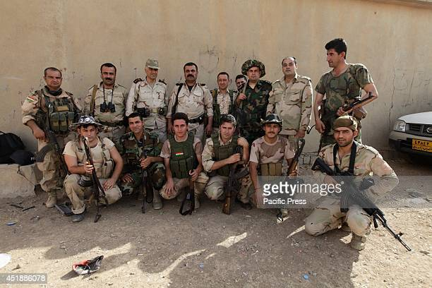Fontline Peshmerga troops based in a home now turned fortifications pose for a group shot before preparations are made for night defenses against...