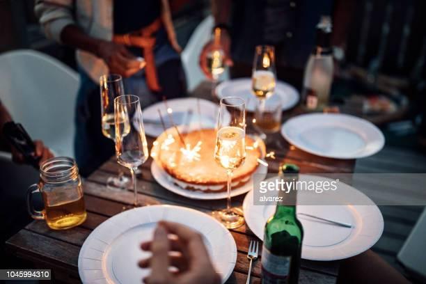 essen und trinken am tisch mit wunderkerzen auf party auf dem dach - geburtstag stock-fotos und bilder