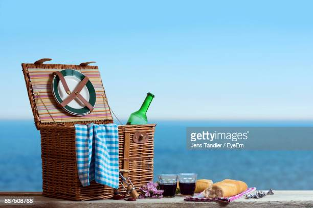 Food And Drink With Picnic Basket On Table By Sea Against Clear Sky