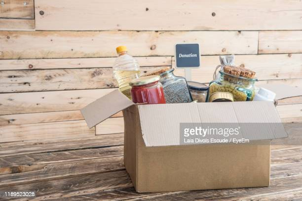 food and drinks in cardboard box on table - charitable donation stock pictures, royalty-free photos & images