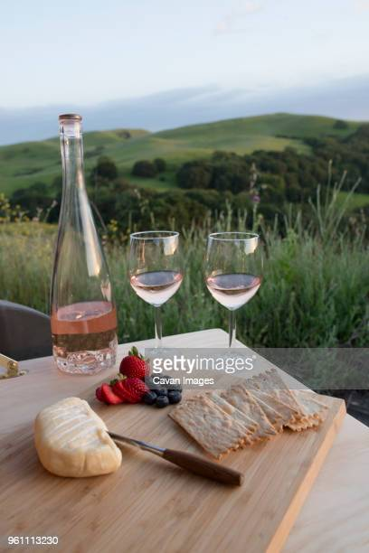 Food and wine on wooden plank outside SUV against rolling landscape