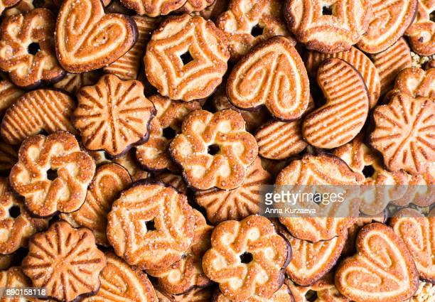 food background with cookies dipped in dark chocolate and sprinkled with sugar, top view - cracker snack stock photos and pictures
