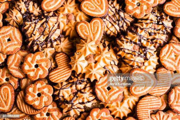 Food background with cookies dipped in dark chocolate and sprinkled with sugar, top view