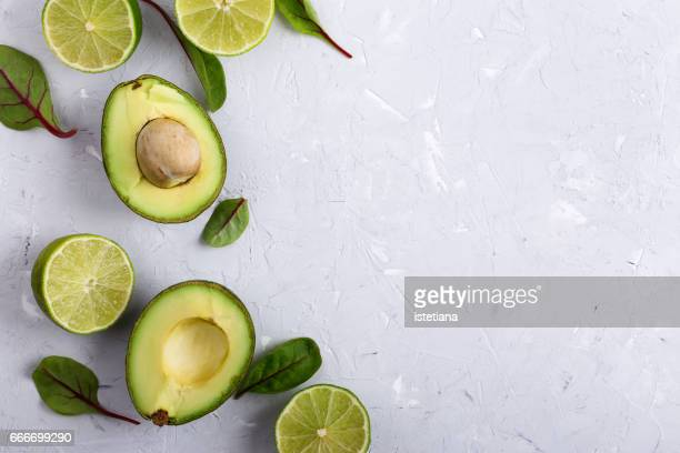 Food background with fresh organic avocado and lime over light gray plaster texture table