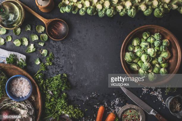 food background with organic brussels sprouts, wooden cooking spoon and ingredients - kitchen background stock pictures, royalty-free photos & images