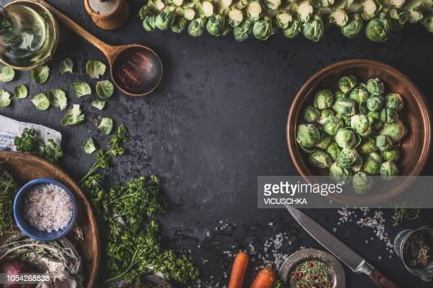 food background with organic brussels sprouts, wooden cooking spoon and ingredients - zutaten stock-fotos und bilder