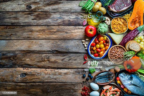 food backgrounds: large variety of food on rustic wooden table. copy space - food pyramid stock pictures, royalty-free photos & images