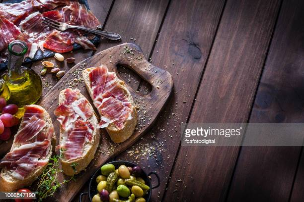 food backgrounds: preparing iberico ham sandwich/spanish bocadillo de jamon iberico - delicatessen stock pictures, royalty-free photos & images