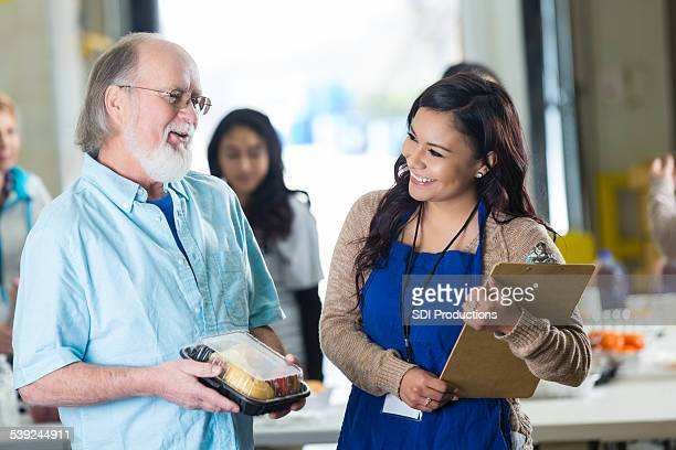 food bank director serving meal to senior man while volunteering - depression bread line stock pictures, royalty-free photos & images