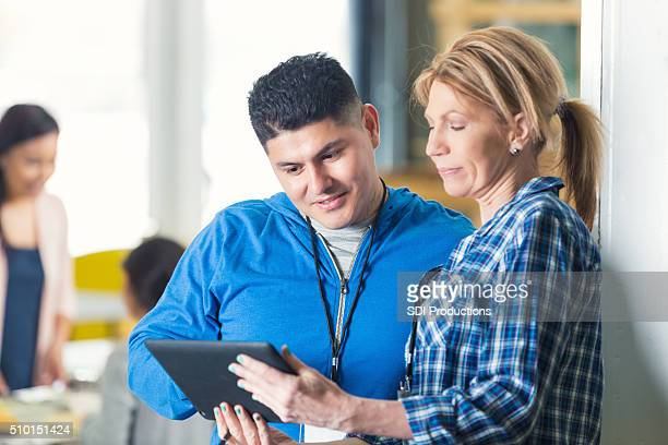 food bank directors check inventory on digital tablet - non profit organization stock pictures, royalty-free photos & images