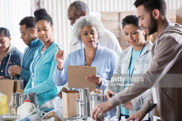 food bank manager instructs volunteers - non profit organization stock pictures, royalty-free photos & images